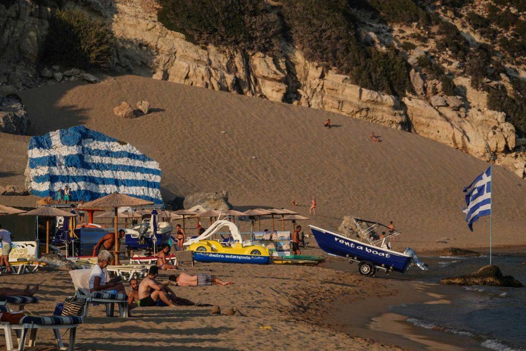 Символ пляжа Цамбика нарисованный греческий флаг осколке скалы