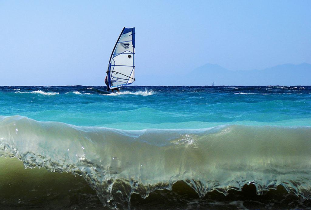 Серфер в волнах Эгейского моря на курорте Иксия